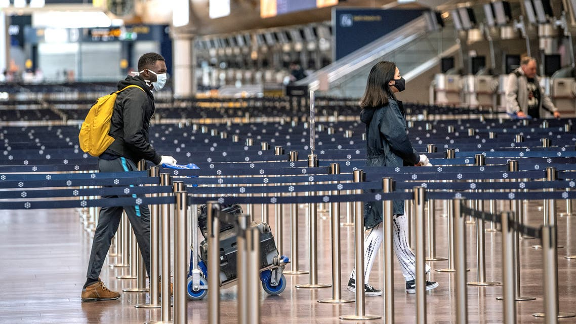 Passengers are pictured wearing protective masks at the Arlanda airport, north of Stockholm, while the spread of the coronavirus disease (COVID-19) continues in Stockholm, Sweden. (Reuters)