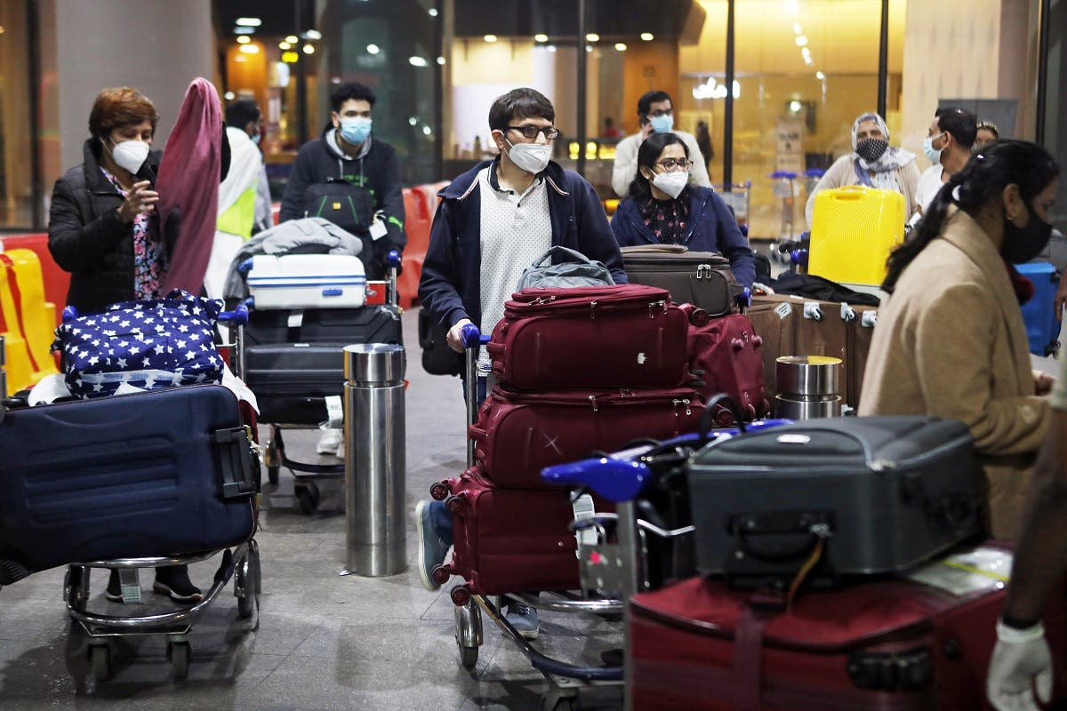 Passengers wearing protective face masks wait to exit upon arrival at Chhatrapati Shivaji Maharaj International Airport after India cancelled all flights from the UK over fears of a new strain of the coronavirus, in Mumbai, India, December 22, 2020. (Reuters)
