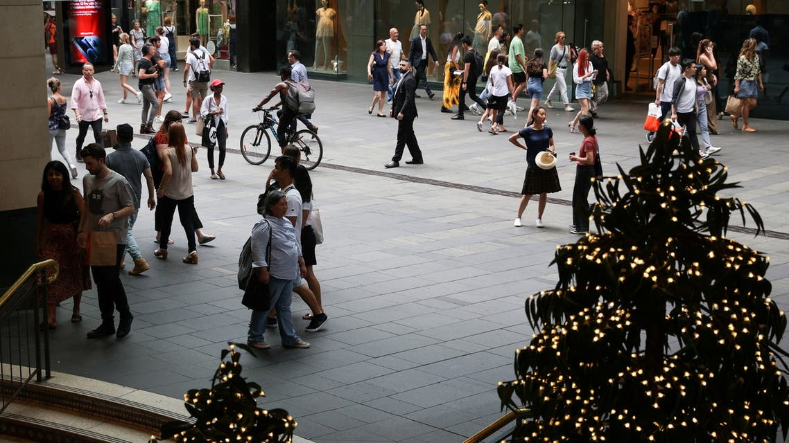 People walk through a shopping plaza decorated for the holidays in the city centre of Sydney. (Reuters)