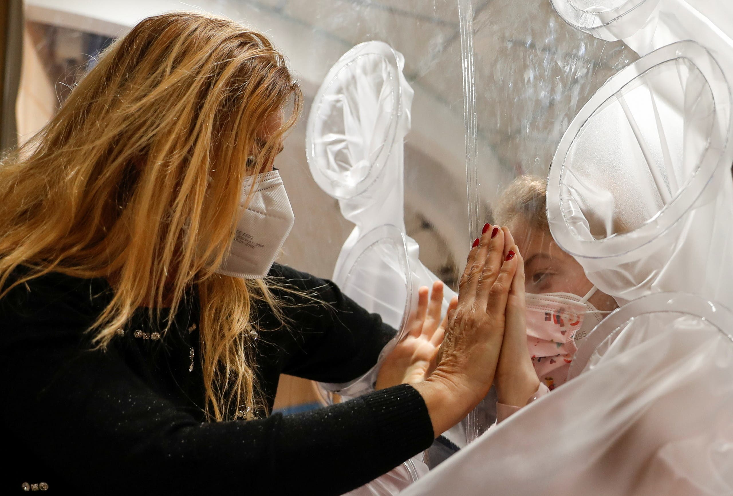 Hospitalized children hug their relatives through a plastic protection, in Rome. (Reuters)
