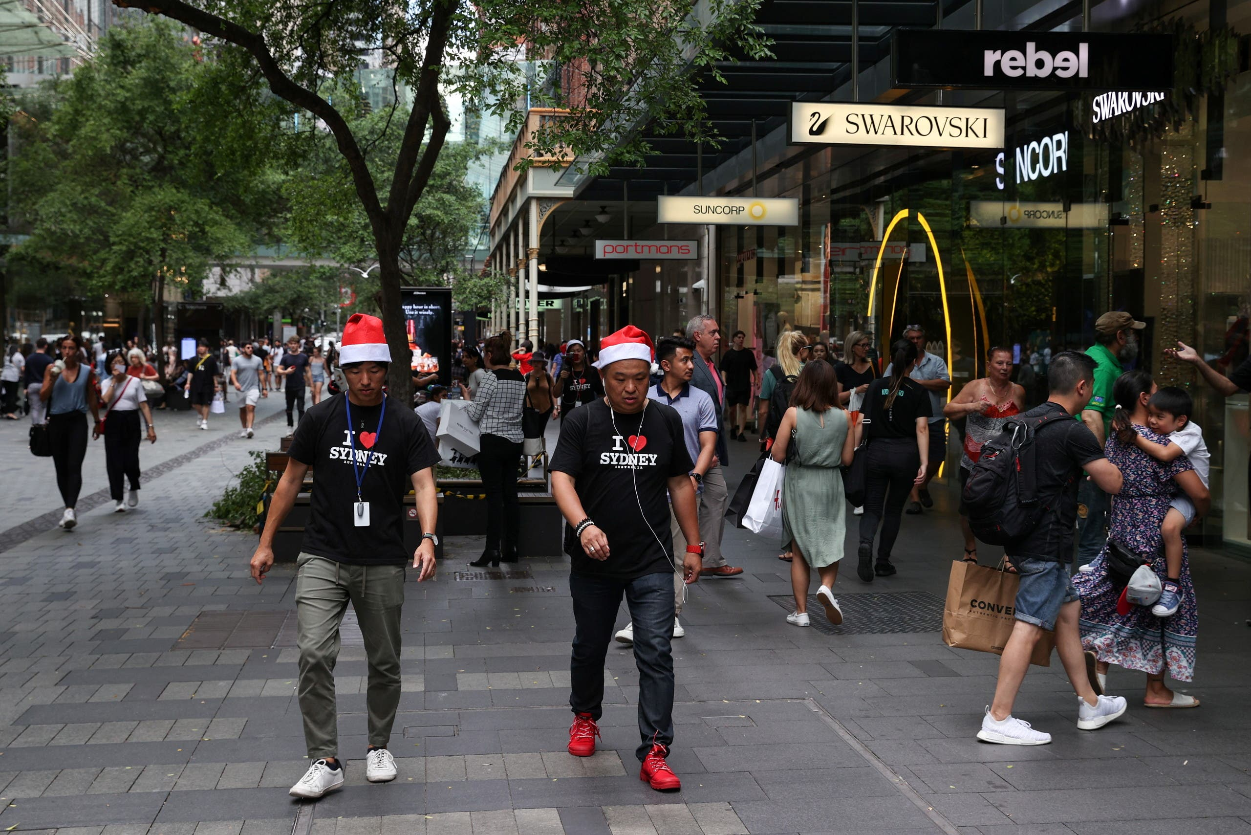 People wearing Santa hats walk through a shopping plaza decorated for the holidays in the city centre of Sydney, Australia, on December 17, 2020.(Reuters)