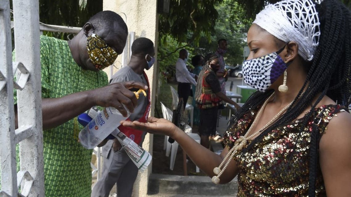 A woman wearing face mask sanitise her hands outside the St. Agnes Catholic Church, Maryland in Lagos, Nigeria. (AFP)