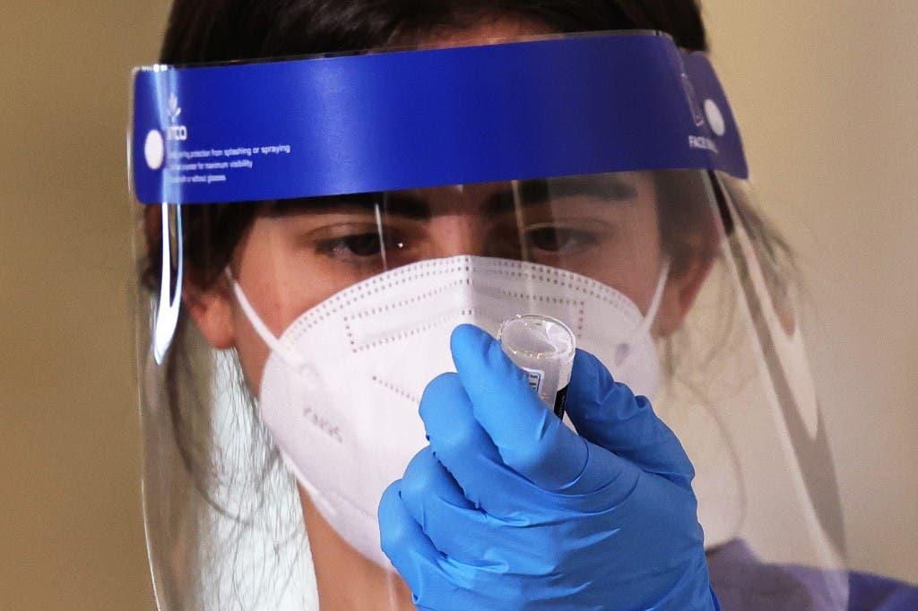 عنصر من الفريق الطبي تحمل عينة من لقاح فايزر ضد كوفيد 19 في نيويورك - فرانس برس