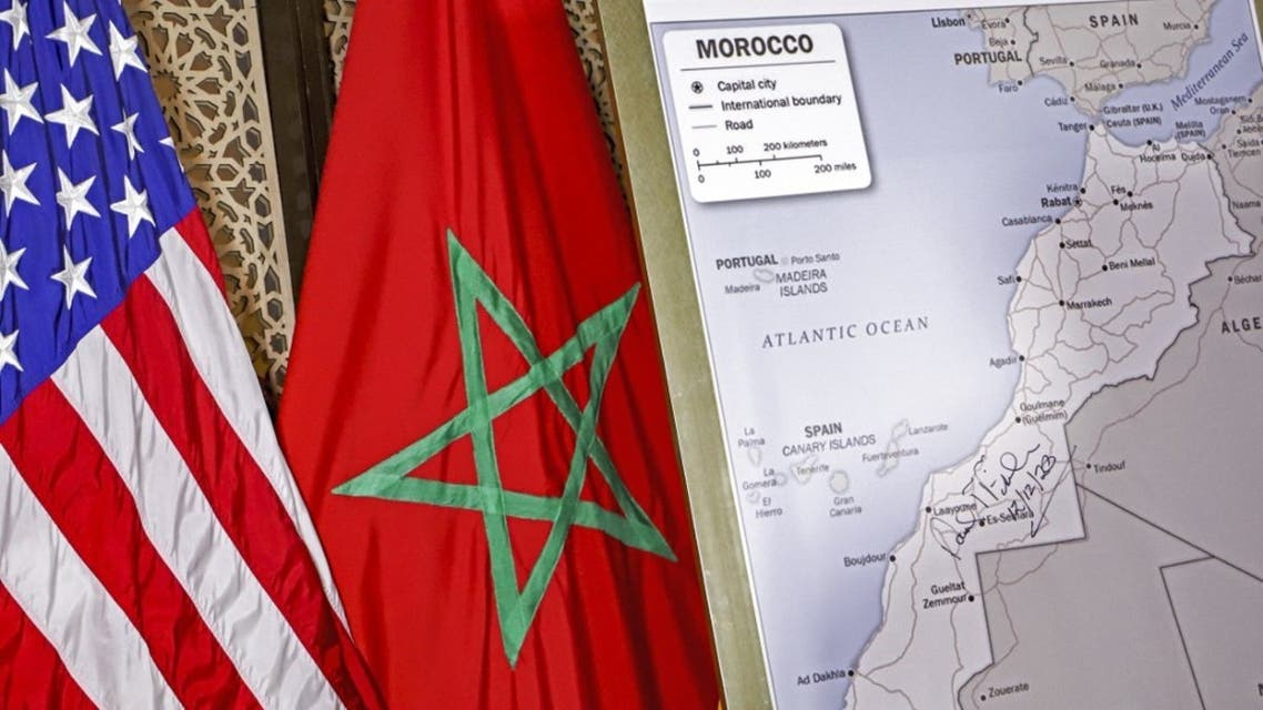 This file photo taken on December 12, 2020 shows (L to R) US and Moroccan flags next to a US State Department-authorised map of Morocco recognising the internationally-disputed territory of the Western Sahara (bearing a signature by US Ambassador to Morocco David T. Fischer) as a part of the North African kingdom, in Morocco's capital Rabat. (AFP)