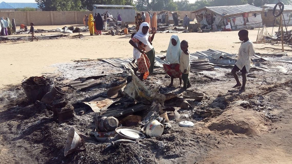 People stand amid the damage at a camp for displaced people after an attack by suspected Boko Haram insurgents in Dalori, Nigeria. (File photo: Reuters)