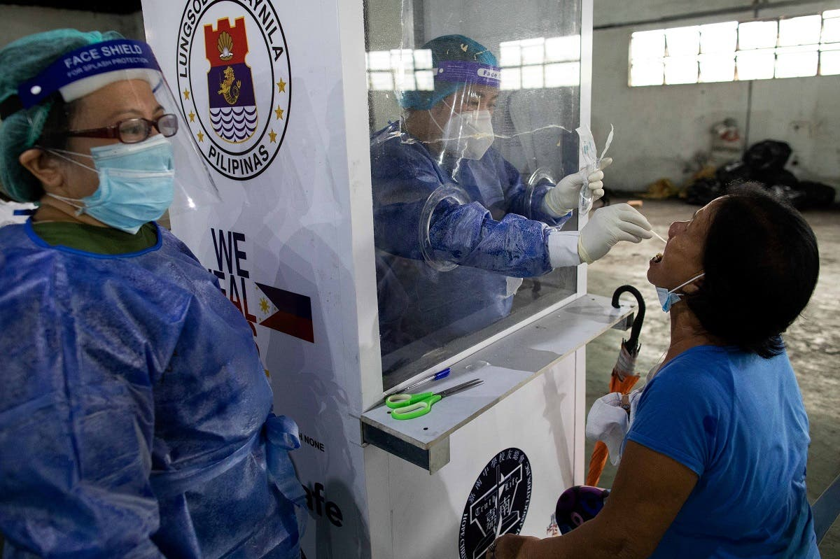 A healthcare worker performs a swab test to a vendors at Pritil Public Market amid the coronavirus disease (COVID-19) outbreak, in Tondo, Manila, Philippines, October 8, 2020. (Reuters/Eloisa Lopez)