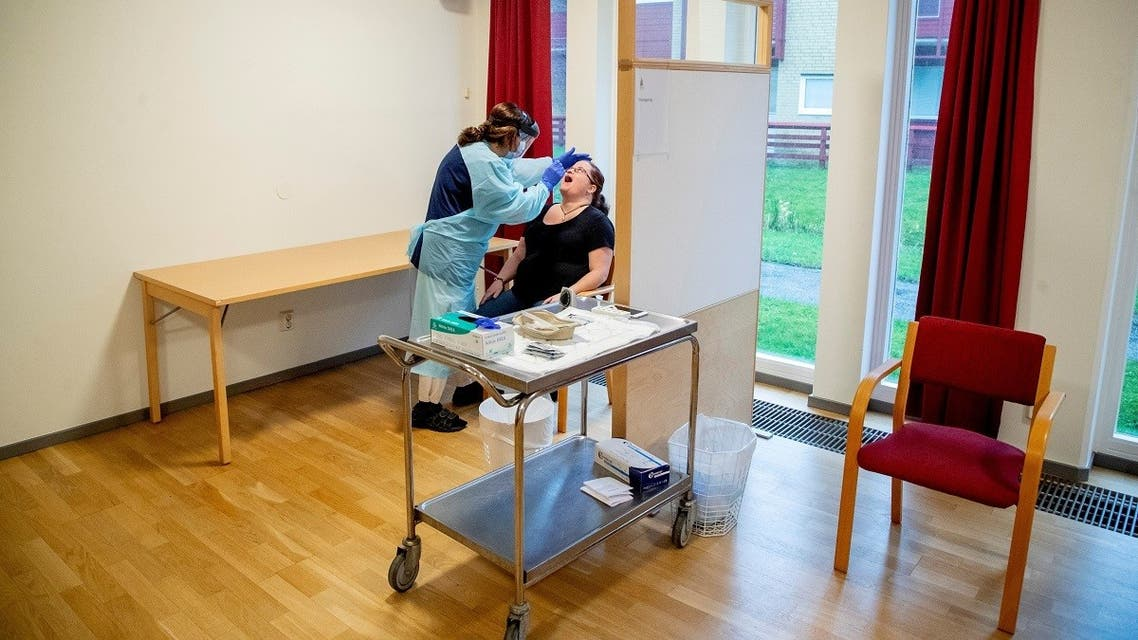 Nurse takes a sample from a nursing aide for a rapid COVID-19 test before she can start her shift at a home for elderly in Lerum, Sweden December 18, 2020. (TT News Agency/Adam Ihse via Reuters)