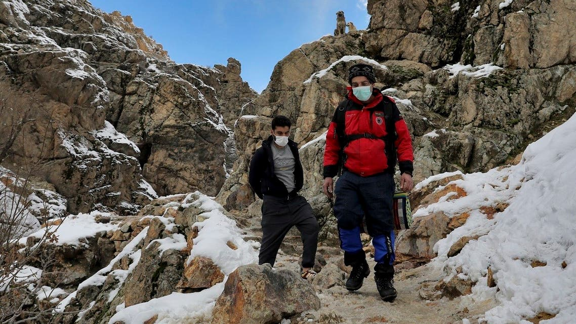 People wearing protective masks hike at the Darakeh mountainous area, north of the capital Tehran, Iran, Friday, Dec 25, 2020. (AP/Ebrahim Noroozi)