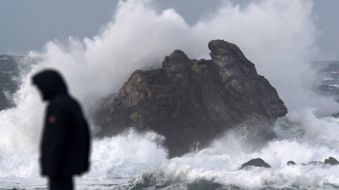 A man walks as high waves crash at Porspoder, western France on December 27, 2020, as Storm Bella strikes the coast of Britanny. (Fred Tanneau/AFP)
