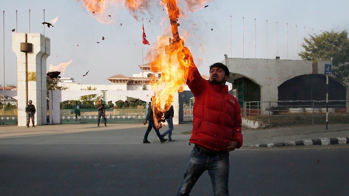 A Nepalese protester burns an effigy of prime minister Khadga Prasad Oli in front of the parliament building in Kathmandu, Nepal, Sunday, Dec. 20, 2020. (AP/Niranjan Shrestha)