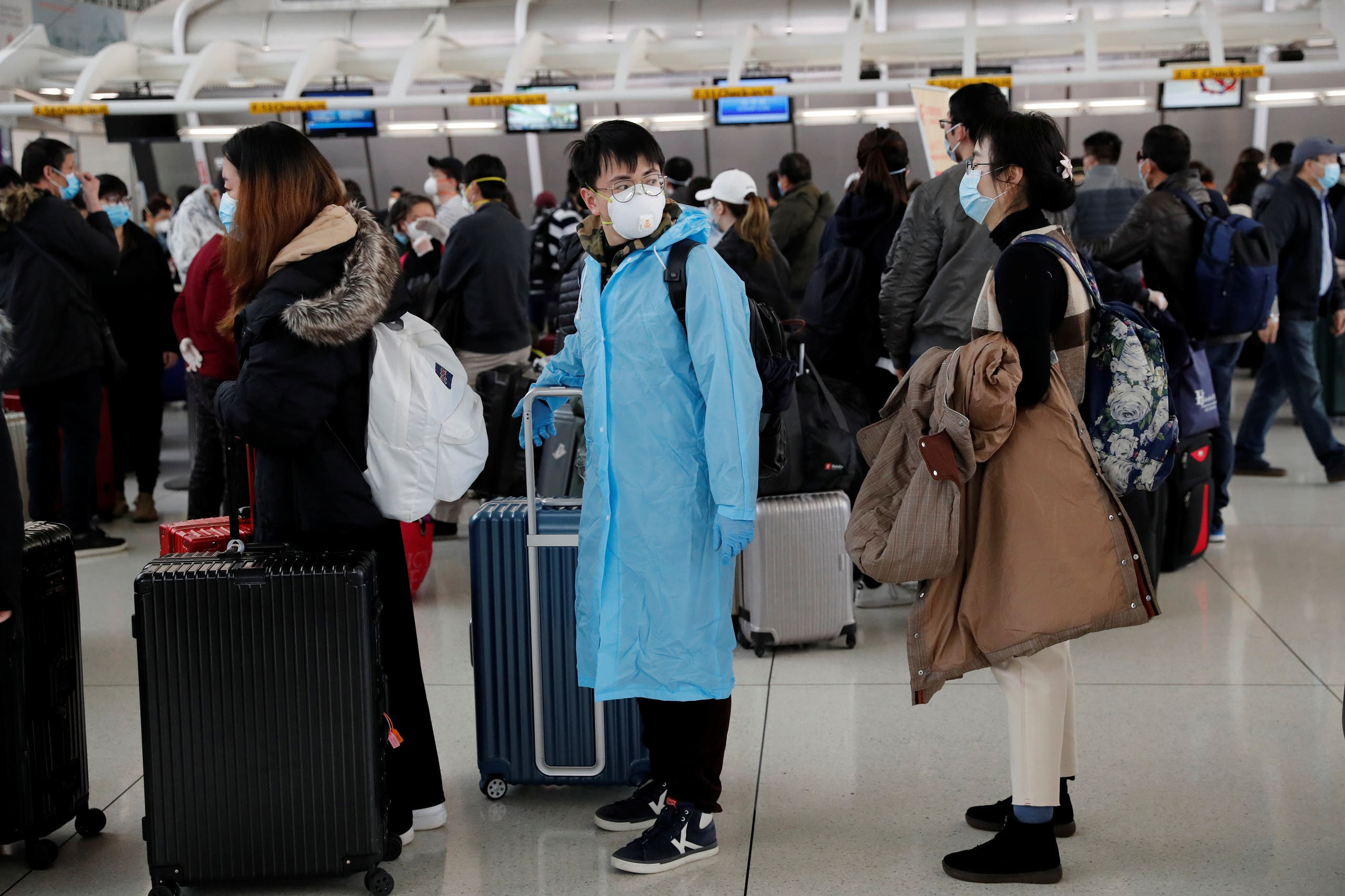 Passengers waiting to check in for an Air China flight are seen with face masks on. (Reuters)