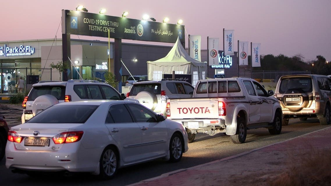 Kuwaitis line up for a PCR test at a COVID-19 drive-thru testing centre near Kuwait International Airport. (AFP)