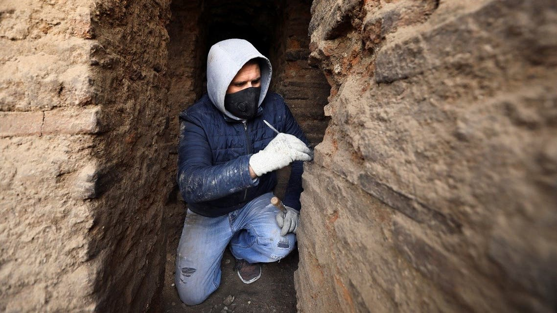 An archaeologist excavates at a Roman archaeological site discovered during works to install a water drainage system, in downtown Amman, Jordan, on December 27, 2020. (Reuters)
