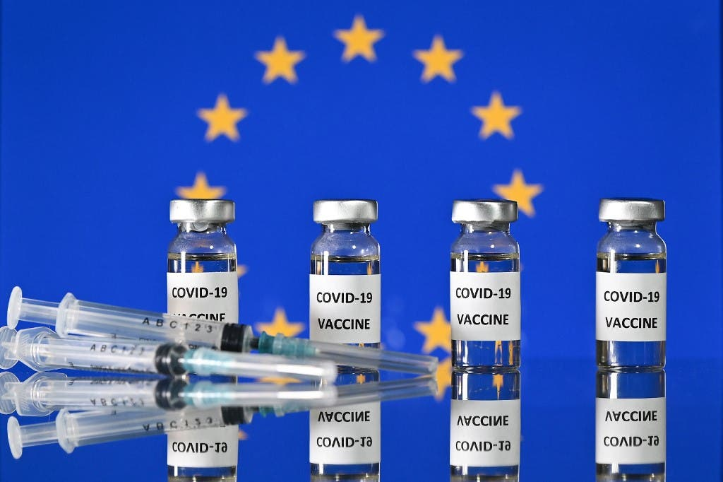 Vials with Covid-19 Vaccine stickers attached, and syringes, with a flag of the European Union. (AFP)