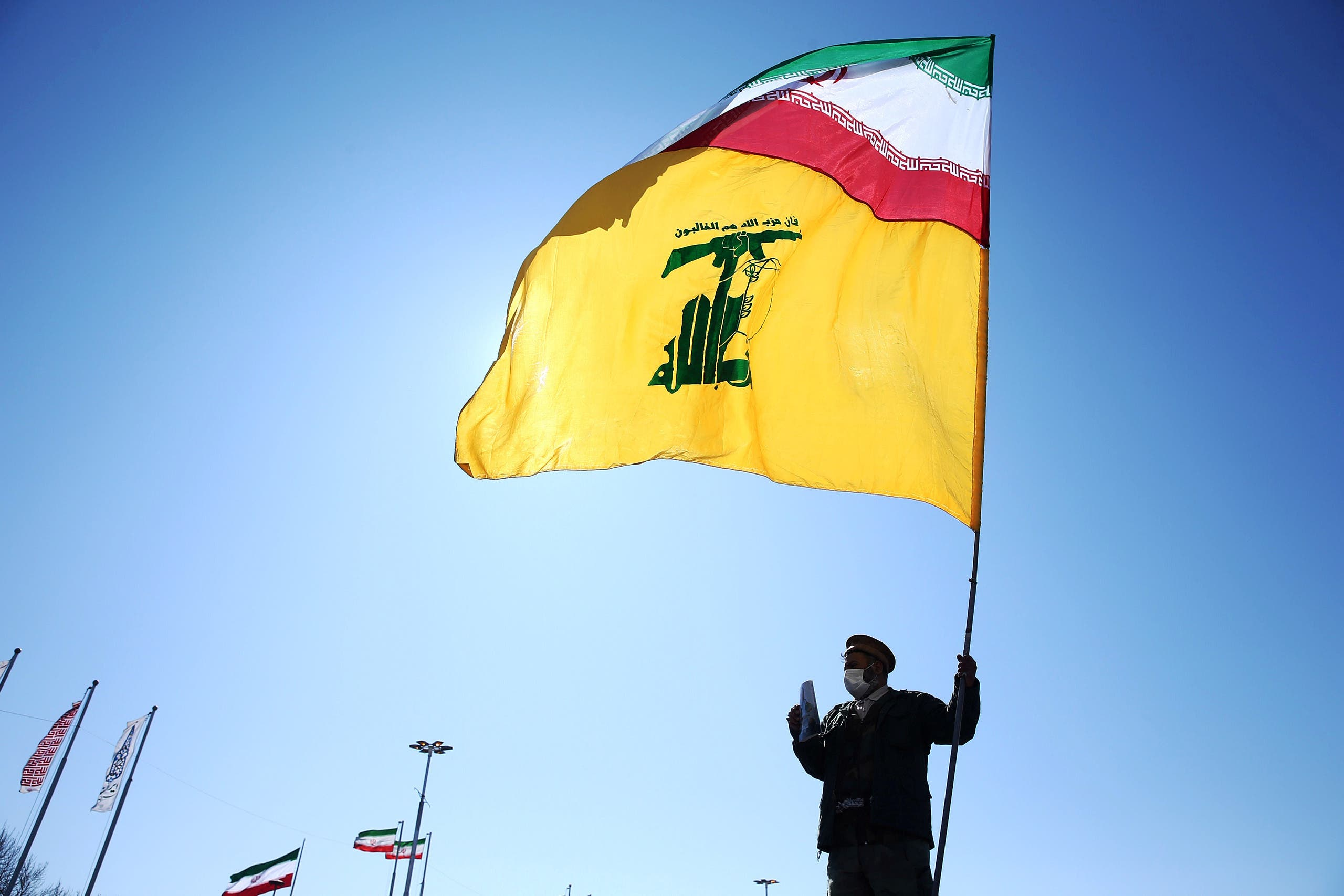 An Iranian holds the flag of Iran and Hezbollah in Tehran (Archive - Reuters)