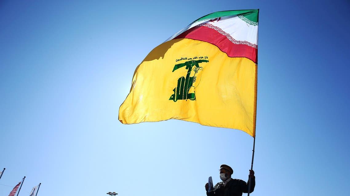إيراني يحمل علم إيران وحزب الله في طهران (أرشيفية- رويترز)
