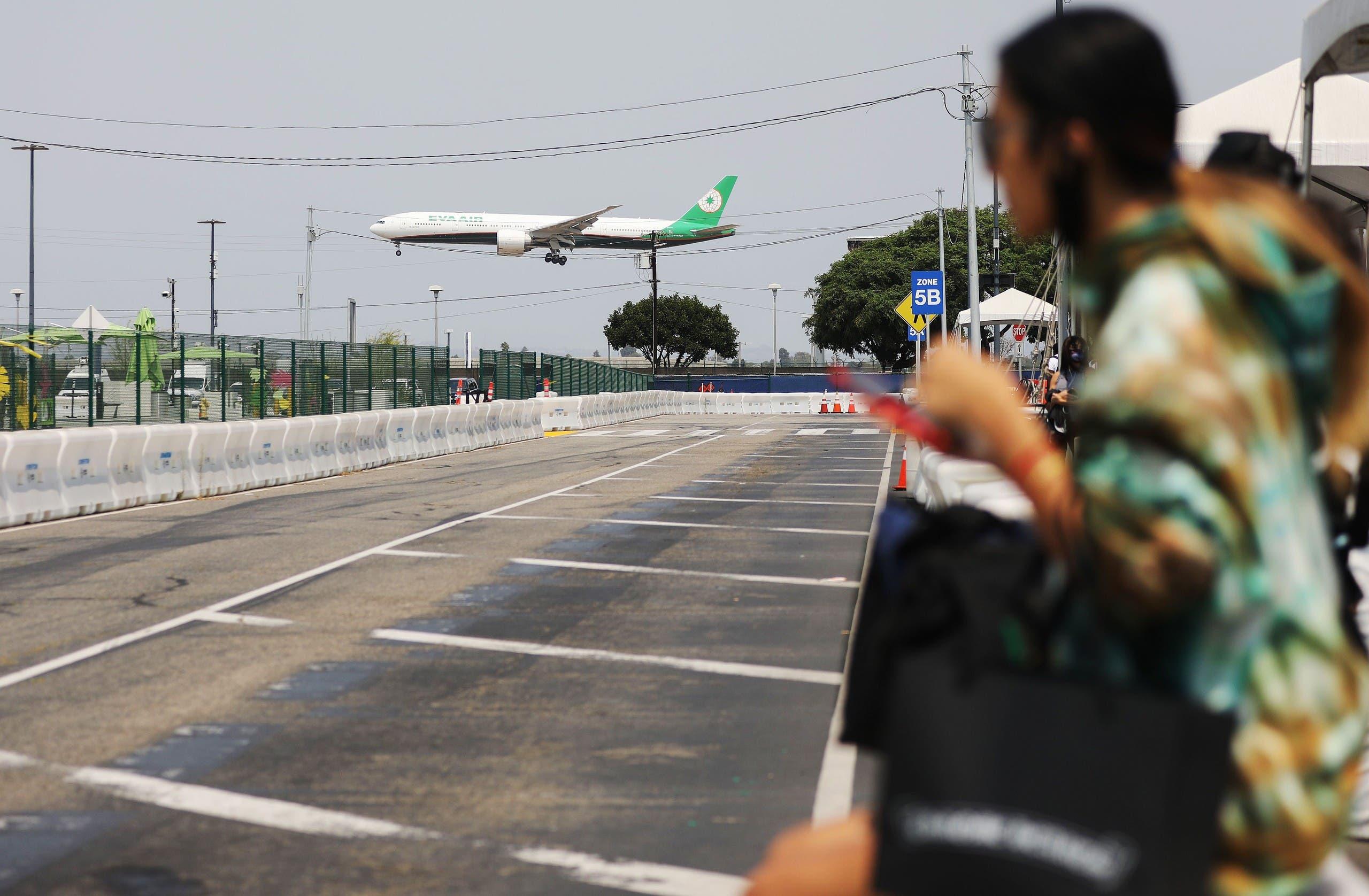 An EVA Air flight lands near a Lyft pickup area at Los Angeles International Airport (LAX) on August 20, 2020. (AFP)