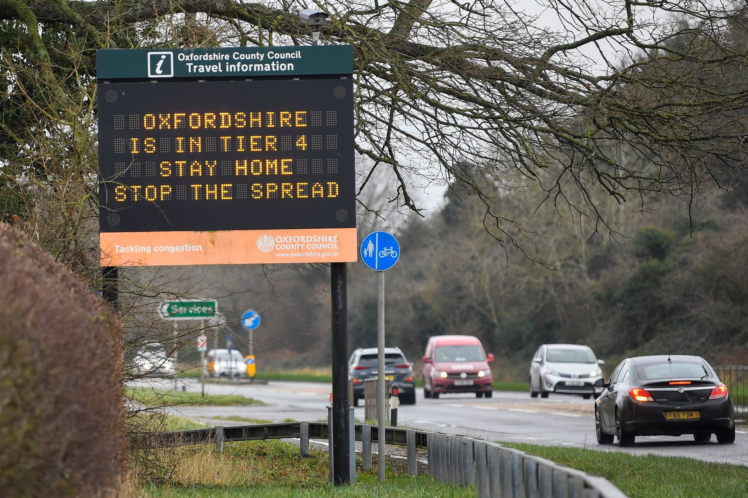 Vehicles drive past a roadside public health information sign, amidst the spread of the coronavirus disease (COVID-19) pandemic, near Oxford, Britain, December 28, 2020. (Reuters)