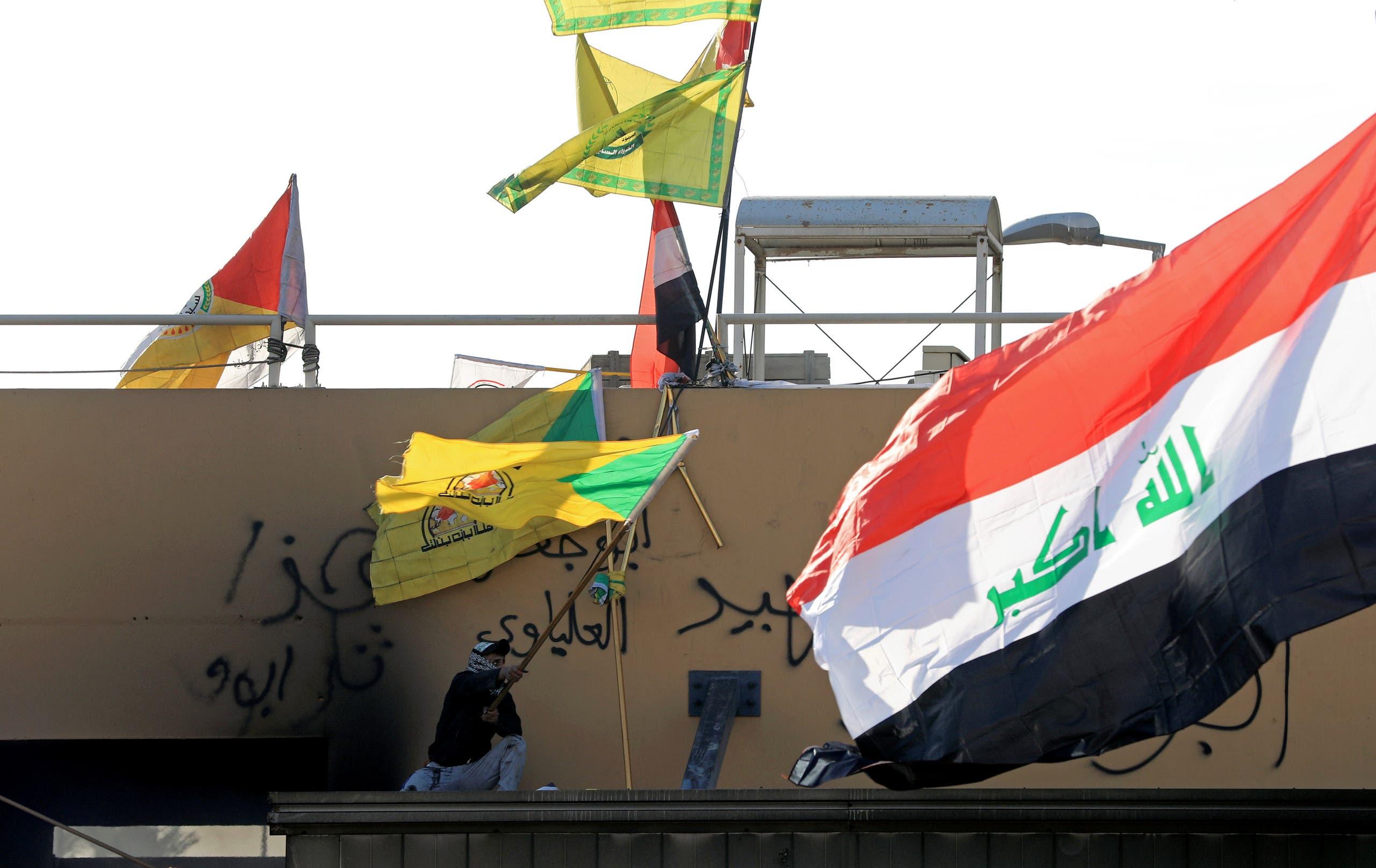علم كتائب حزب الله العراقي أمام السفارة الأميركية في بغداد (أرشيفية- رويترز)