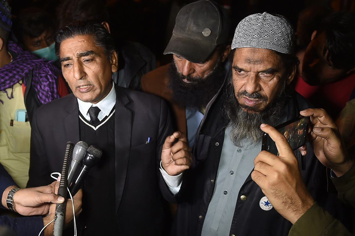 Sheikh Aslam (R), a relative of one of the accused of murdering US journalist Daniel Pearl and his lawyer Nadeem Azhar speak with media representatives outside a prison in Karachi on December 24, 2020. (AFP)