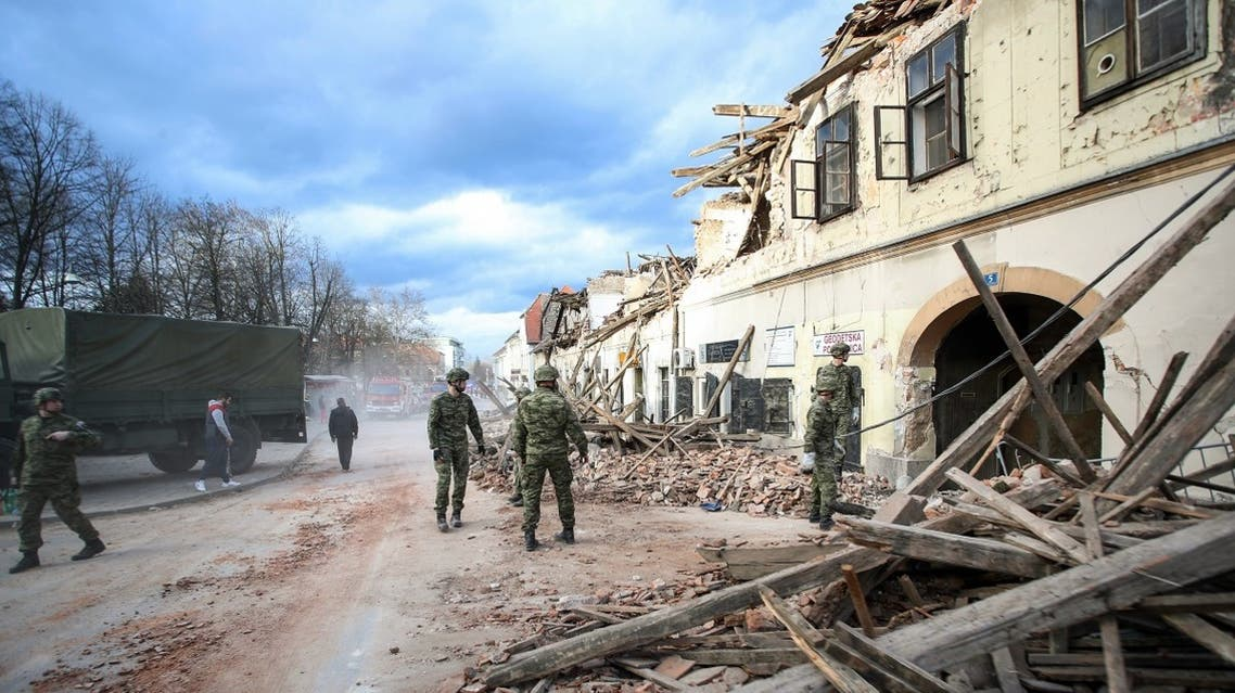 Croatian soldiers stand next wreckage and damaged buildings in Petrinja, some 50kms from Zagreb, after the town was hit by an earthquake of the magnitude of 6,4 on December 29, 2020. (AFP)