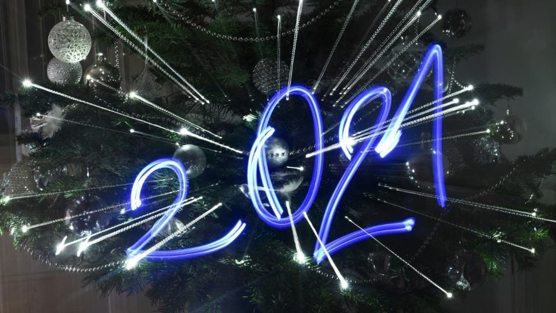 An illustration taken on December 30, 2020 in Budapest shows the numbers of the year 2021 painted with light in front of an illuminated Christmas tree. (AFP)