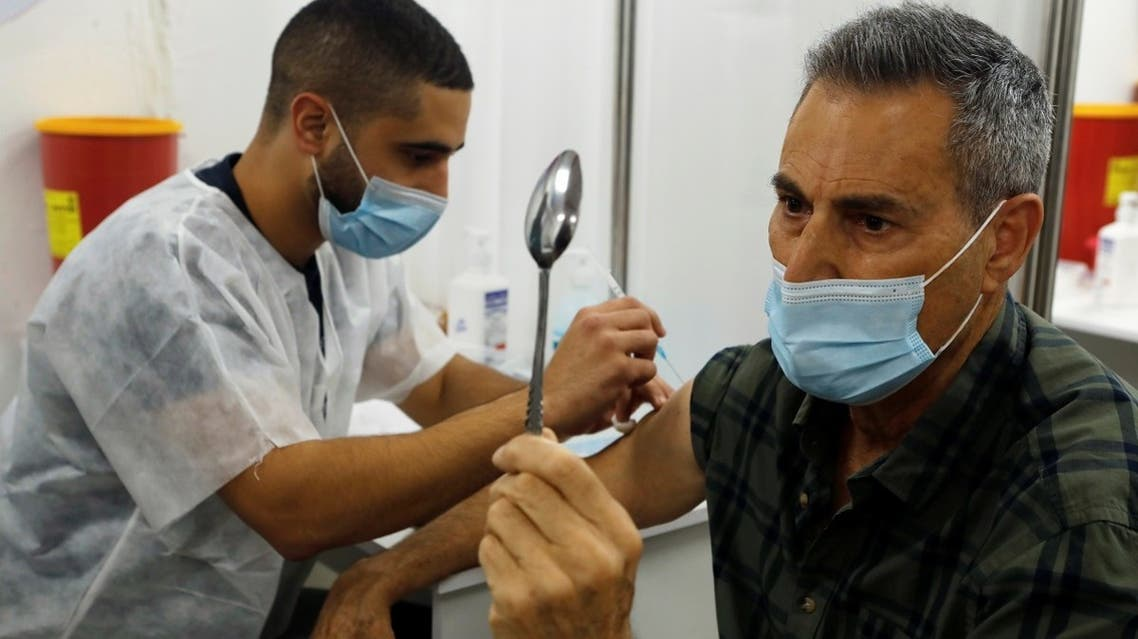 Celebrity mystic Uri Geller holds a spoon as he performs his spoon-bending trick for medical staff while receiving a vaccination against the coronavirus disease, in Jaffa, near Tel Aviv, Israel, on December 31, 2020.  (Reuters)