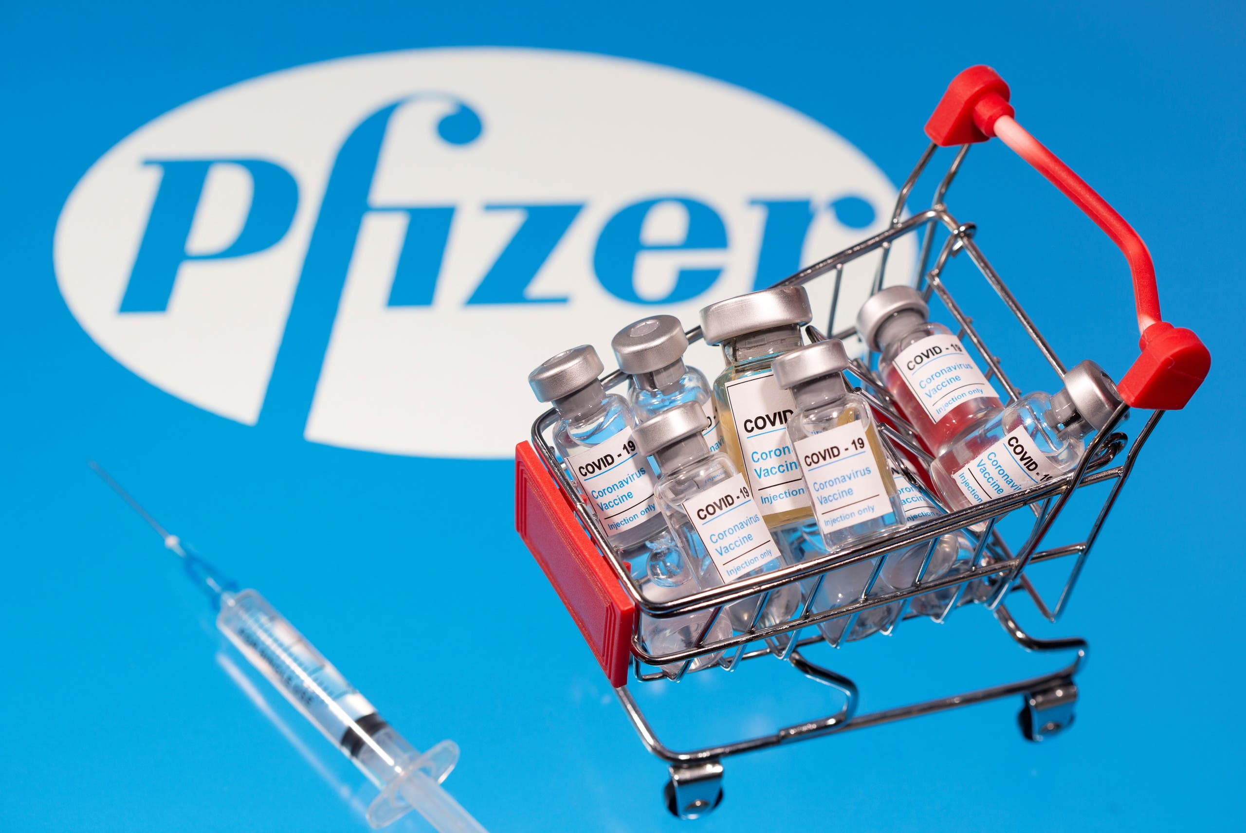 A small shopping basket filled with vials labeled COVID-19 - Coronavirus Vaccine and a medical sryinge are placed on a Pfizer logo in this illustration taken November 29, 2020. (Reuters)