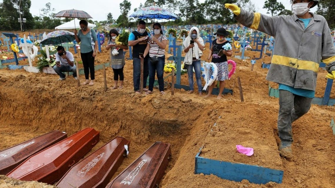 In this file photo taken on May 6, 2020 mourners stand besides a mass grave at the Nossa Senhora cemetary in Manaus, Amazon state, Brazil, amid the COVID-19 coronavirus pandemic. (AFP)