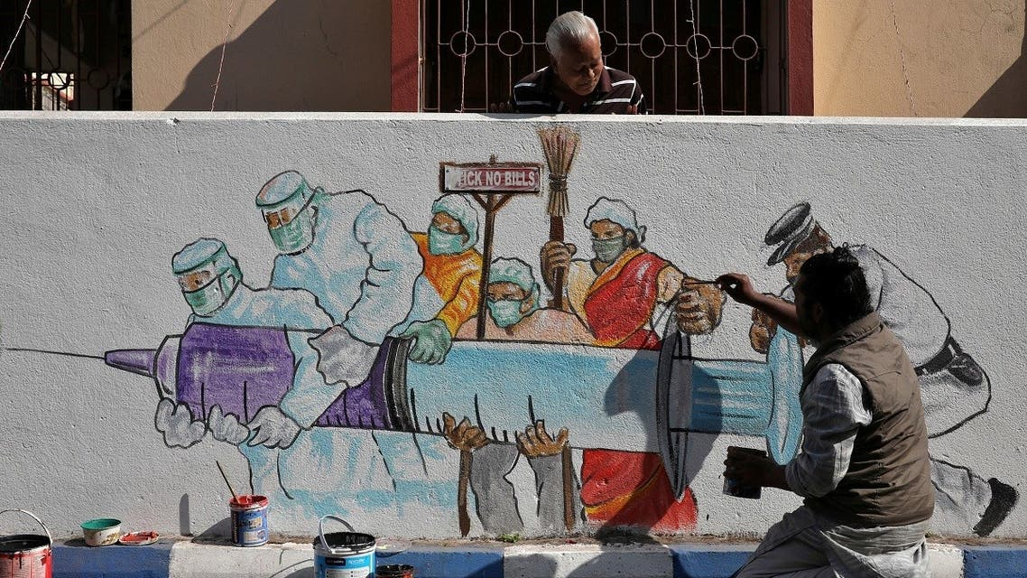 A man applies finishing touches to graffiti representing a vaccine, amidst the spread of coronavirus disease (COVID-19) in Kolkata, India, January 2, 2021. (Reuters/Rupak De Chowdhuri)