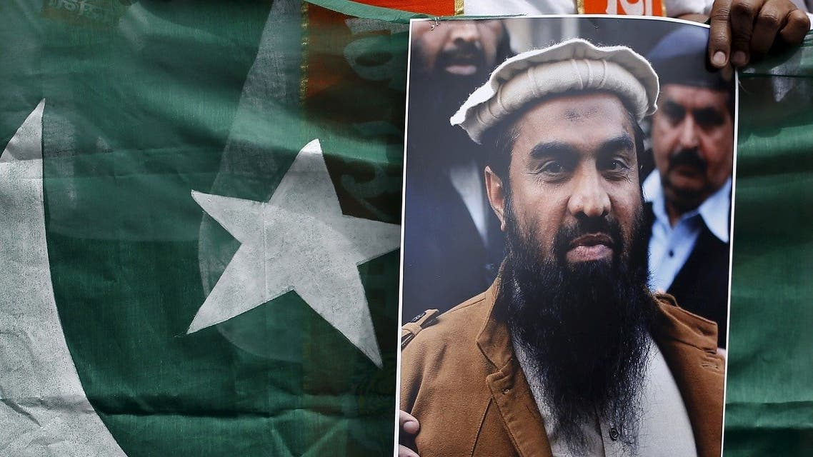 A supporter of Shiv Sena, a Hindu hardline group, holds Pakistan's national flag and a portrait of Zaki-ur-Rehman Lakhvi during a protest against Lakhvi's release, in New Delhi April 11, 2015. (Reuters)