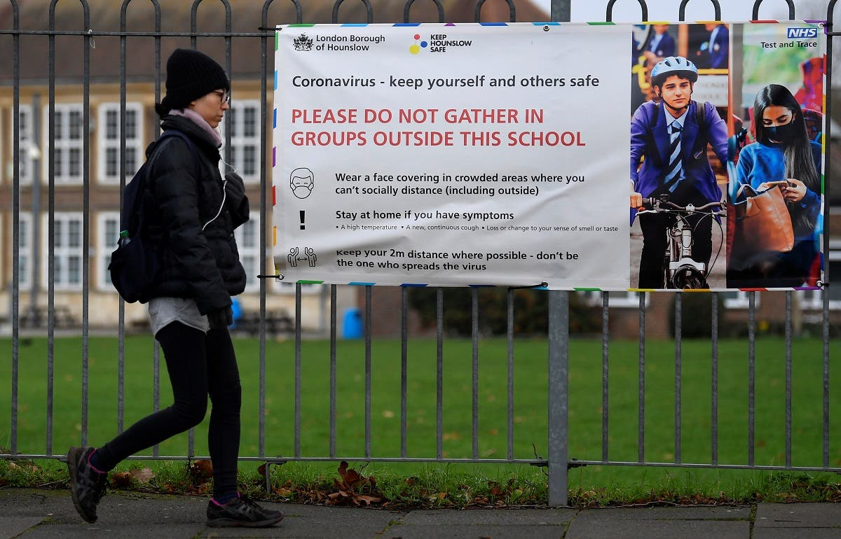 A woman walks past a social distancing health message outside of a secondary school in London. (Reuters)