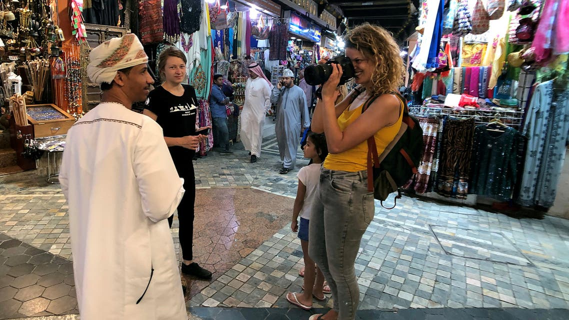 A European tourist takes a photo of an Omani man in a local souq downtown, Muscat, Oman, February 12, 2019. (Reuters)