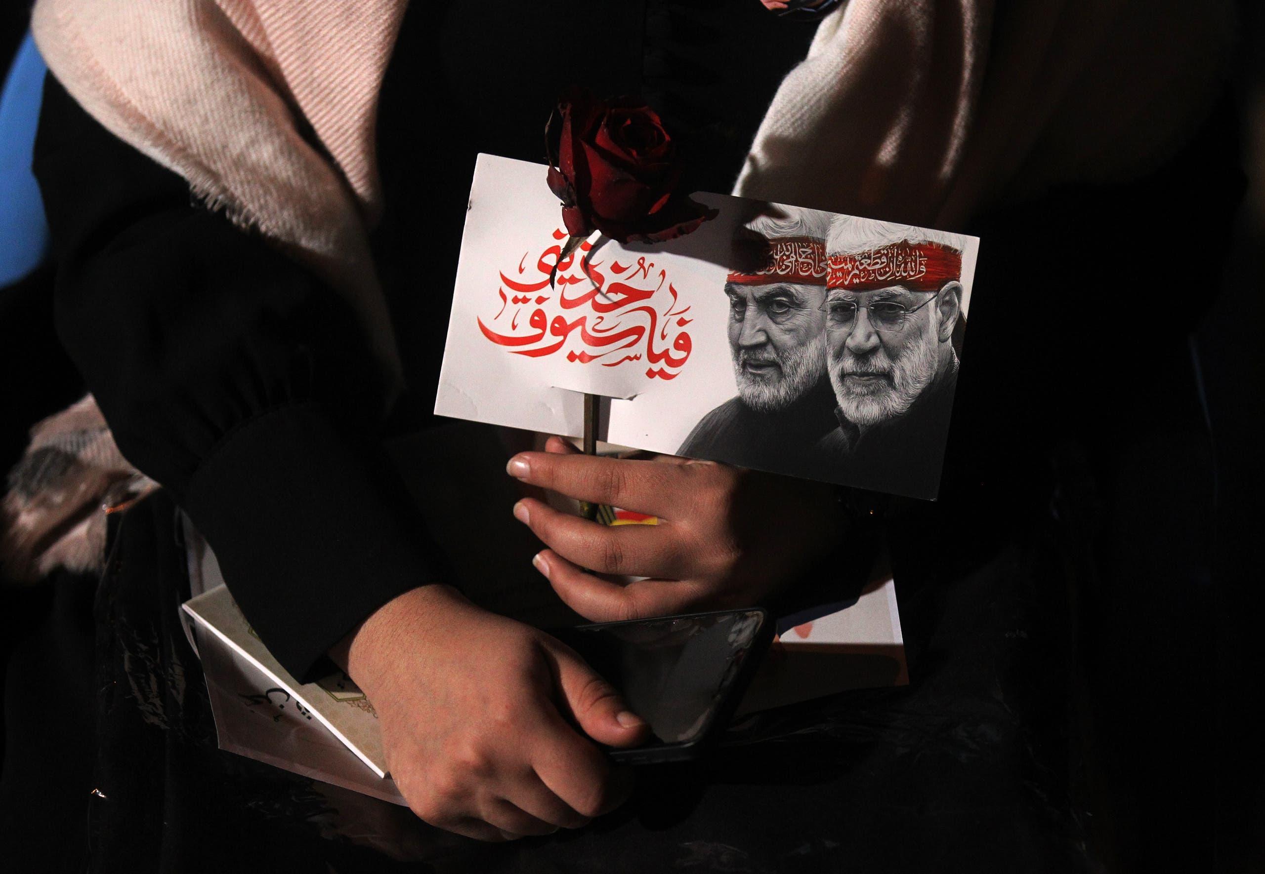 An Iraqi woman carries a portrait of Abu Mahdi al-Mohandes and Qasem Soleimani at Baghdad Airport. (AFP)