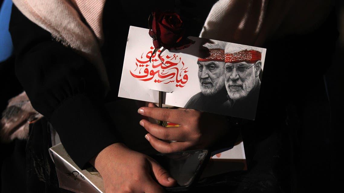 An Iraqi woman carries a portrait of Abu Mahdi al-Muhandis and Qasem Soleimani at Baghdad Airport. (AFP)