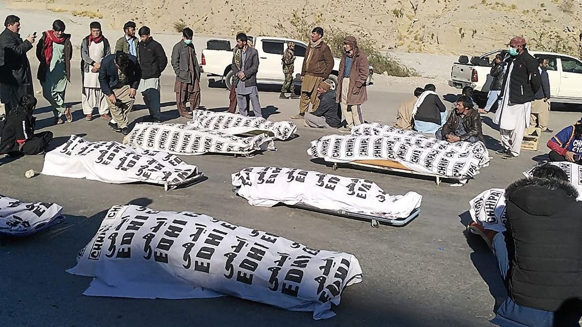 Members of Shia Hazara community stand around the dead bodies after gunmen killed 11 workers of the community in mountainous Machh area, in the Balochistan province, on January 3, 2021. (STR/AFP)