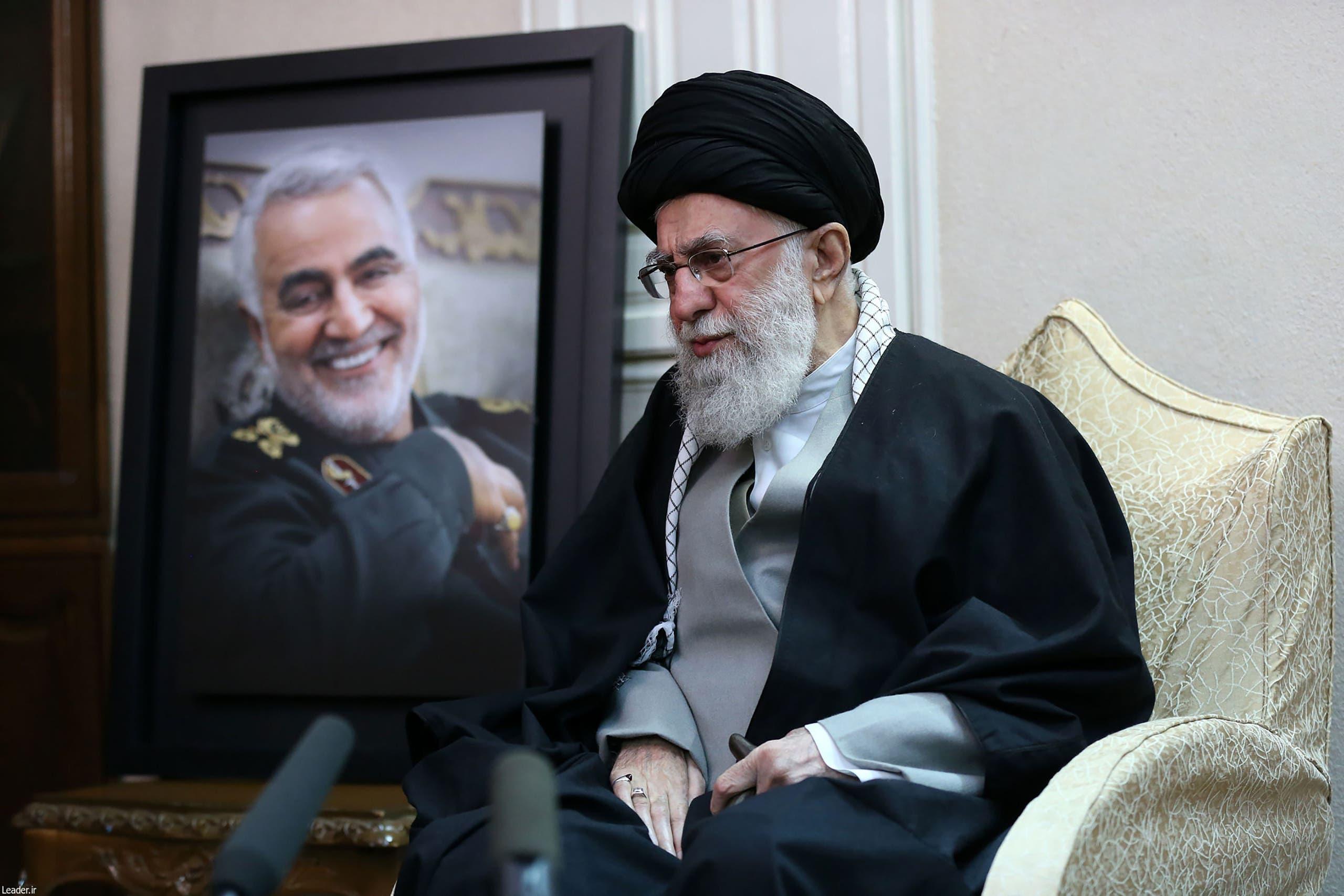 رهبر ایران علی خامنه ای و عکسی از سلیمانی در کنار او (بایگانی - فرانس پرس)