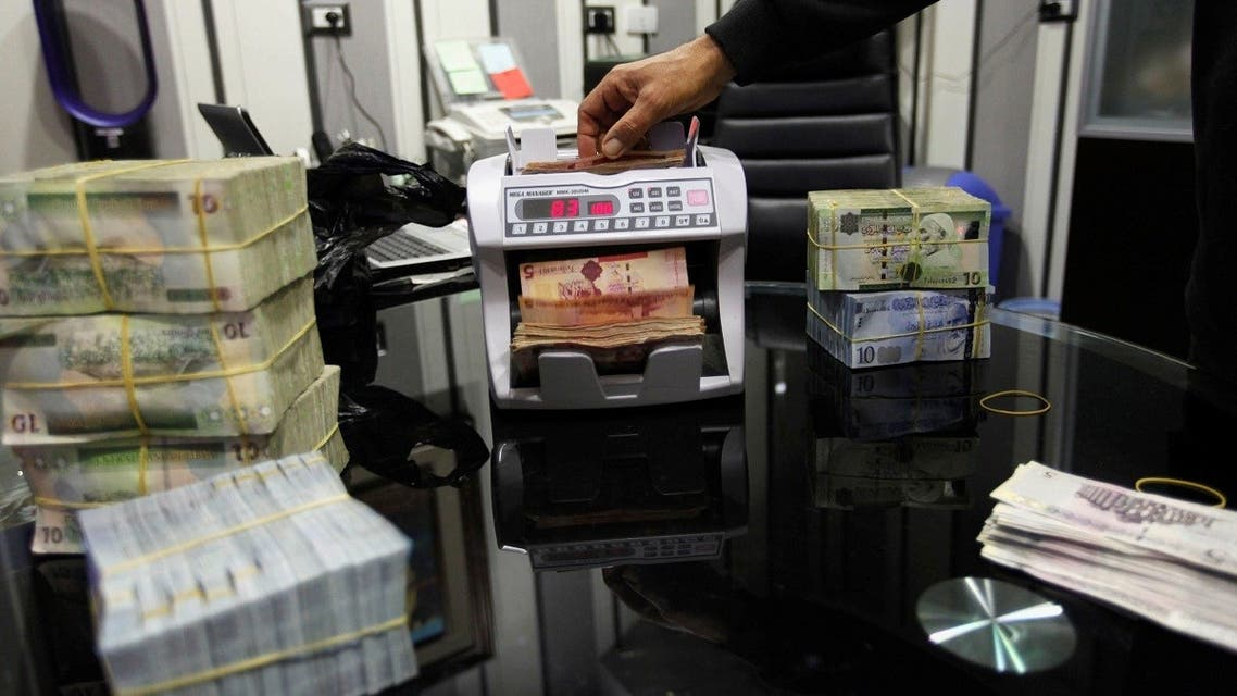 A man uses a currency counting machine to count Libyan dinars at a currency exchange office in Tripoli April 27, 2016. (Reuters/Ismail Zitouny)