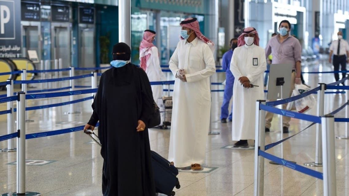 Saudi passengers queue for a temperature check at terminal 5 in the King Fahad International Airport, designated for domestic flights, in the capital Riyadh on May 31, 2020. (AFP)