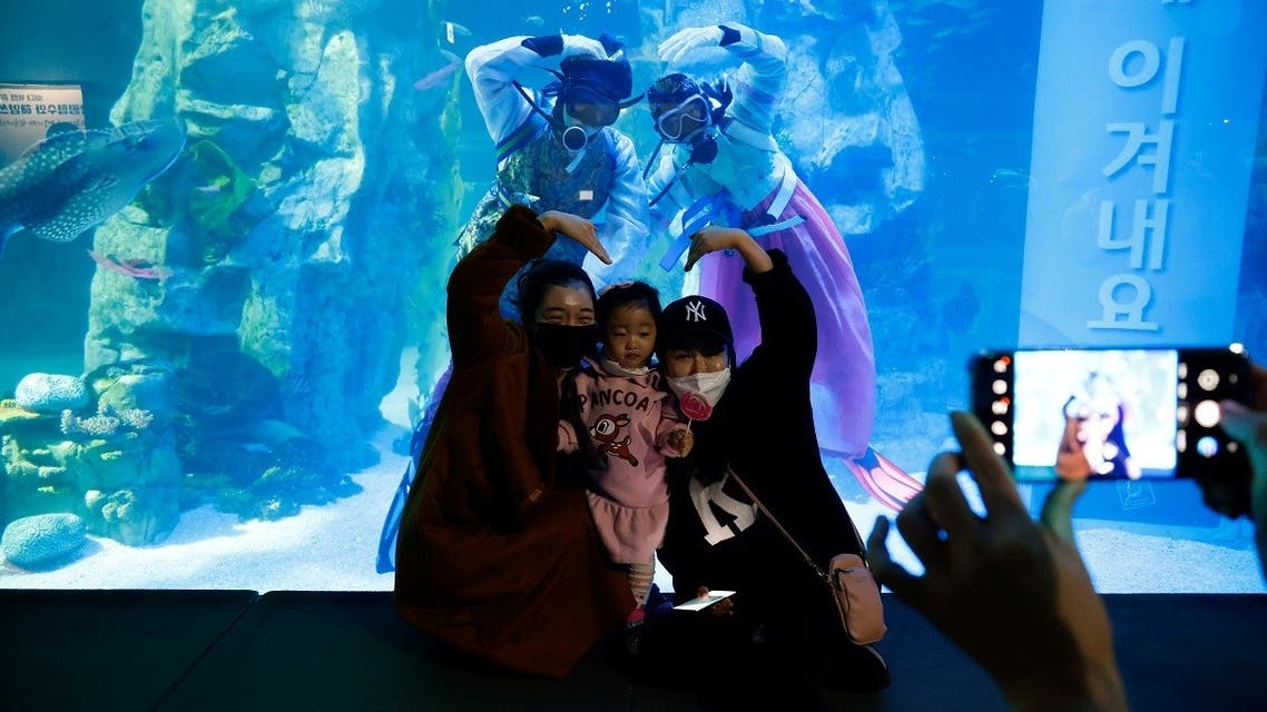 Visitors wearing masks pose for photographs with divers in Korean traditional costumes Hanbok during an event to celebrate New Year. (Reuters)