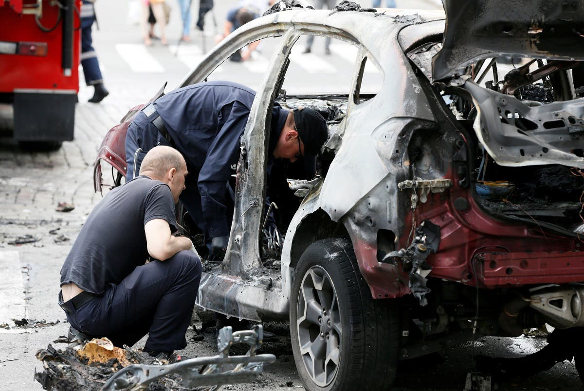 A file photo shows investigators inspect a damaged car at the site where journalist Pavel Sheremet was killed by a car bomb in central Kiev, Ukraine, July 20, 2016. (Reuters/Valentyn Ogirenko)