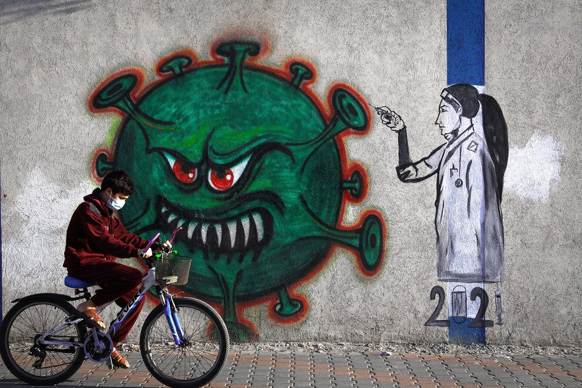 A Palestinian youth wearing a face mask rides his bicycle past a mural painting of a nurse injecting a vaccine to a COVID-19 virus in Gaza City, on December 31, 2020.  (AFP)