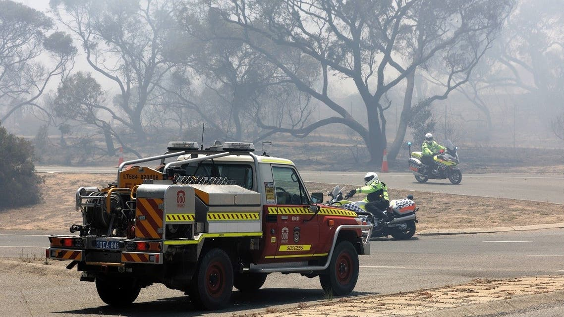 Emergency vehicles patrol the perimeter while battling a bushfire in Kwinana, some 30 kilometers south of Perth on January 4, 2021. (Trevor Collens/AFP)