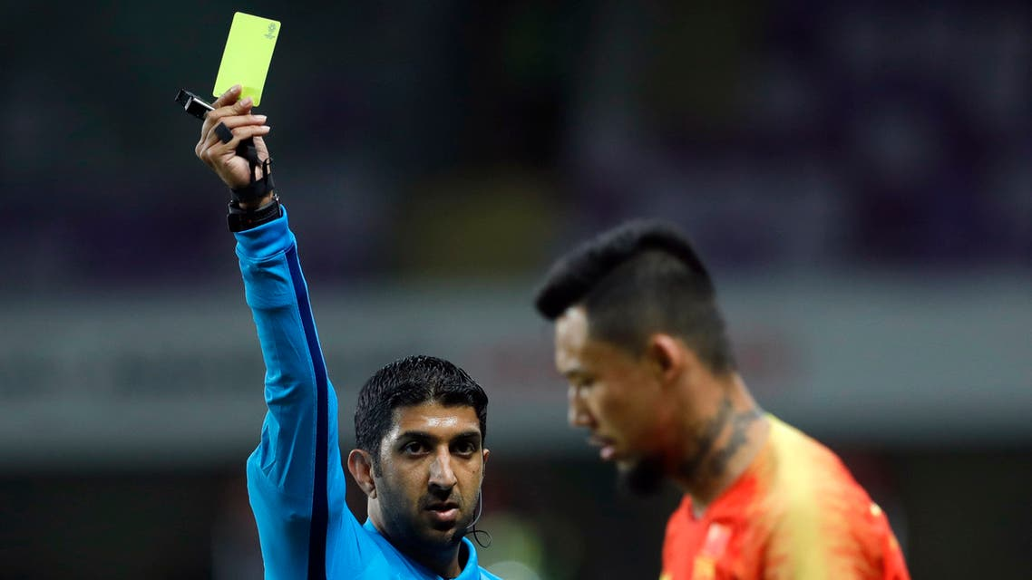 Referee Mohammed Abdulla Hassan, left, shows a yellow card to China's defender Zhang Linpeng during the AFC Asian Cup round of 16 soccer match between Thailand and China at the Hazza Bin Zayed stadium in Al Ain, United Arab Emirates, Sunday, January 20, 2019. (AP Photo)