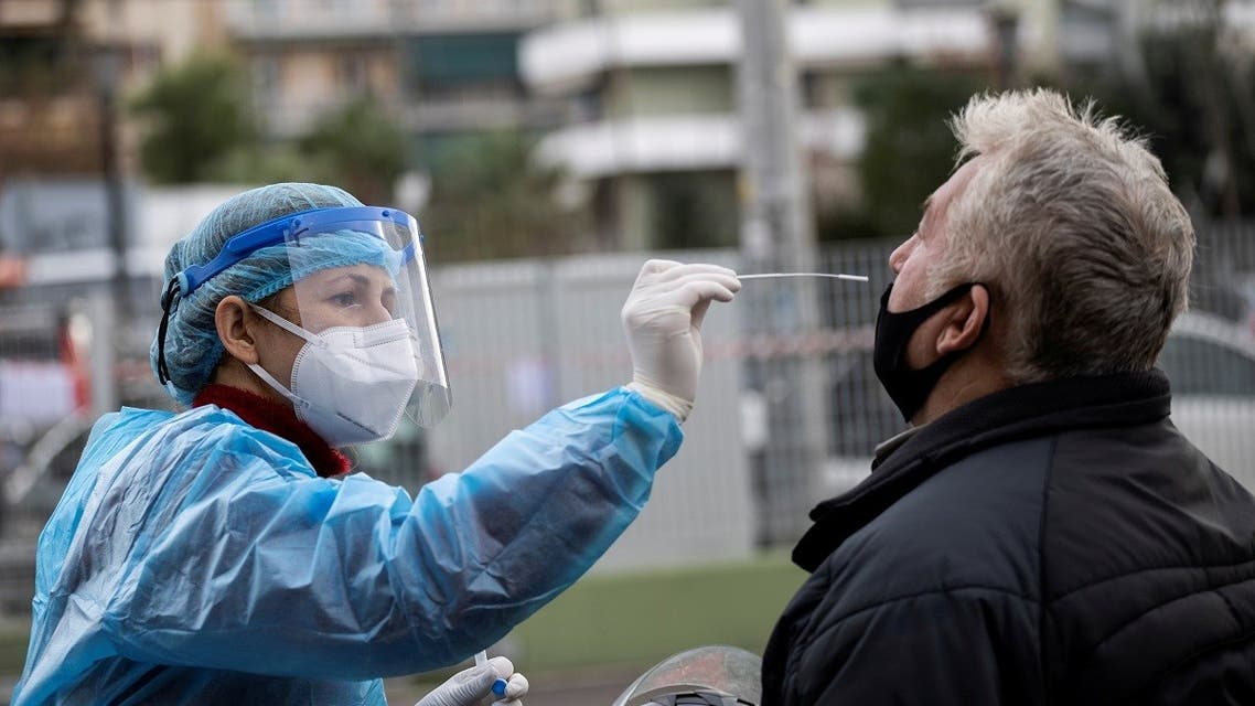 A healthcare worker takes a swab from a man during the coronavirus disease pandemic, in Athens, Greece, Dec. 18, 2020. (Reuters/Alkis Konstantinidis)