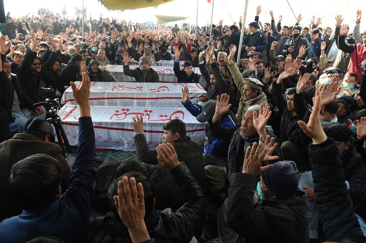 Mourners from Shia Hazara community chant slogans near the coffins of the miners during a sit-in protest. (AFP)