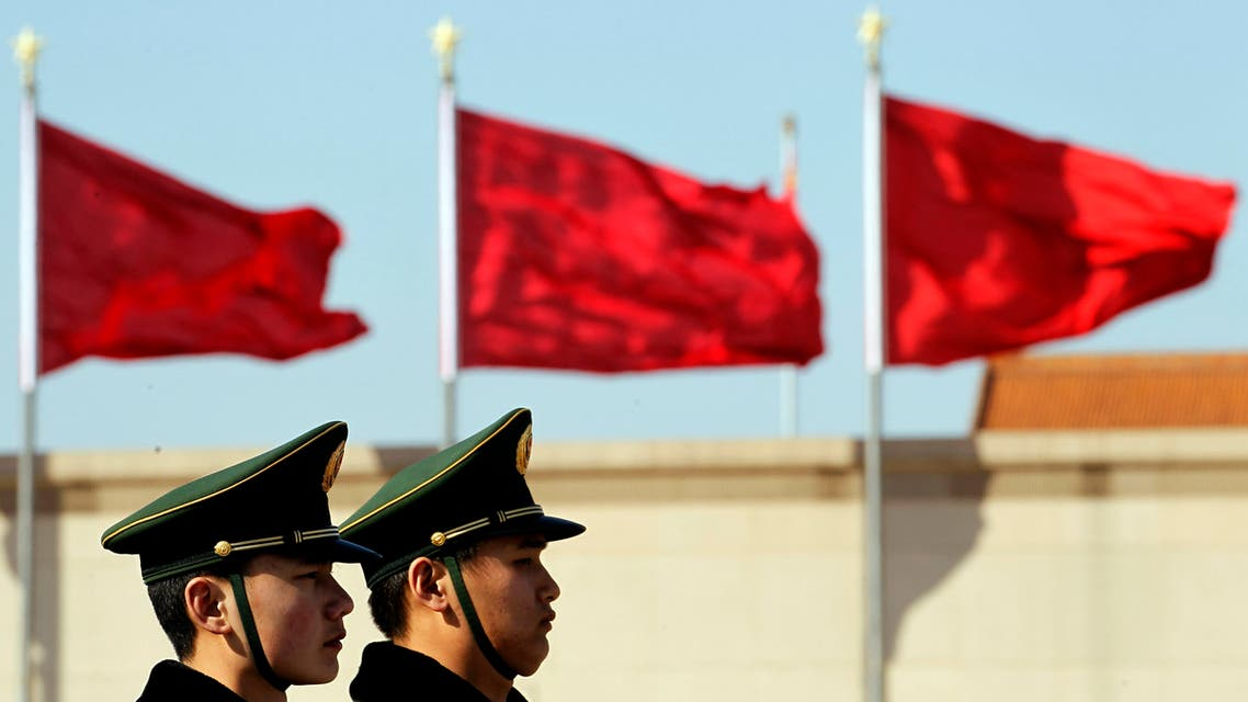 Chinese paramilitary police stand on duty near flags during the fourth plenary session of the National People's Congress held in the Great Hall of the People in Beijing, China, Sunday, March 11, 2012. (AP Photo/Ng Han Guan)