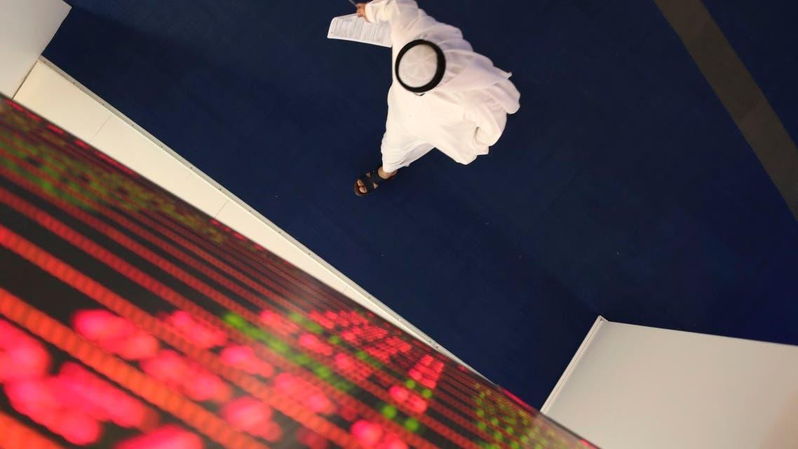 An Emirati trader passes under the stocks display screen at the Dubai Financial Market in Dubai, United Arab Emirates (AP).