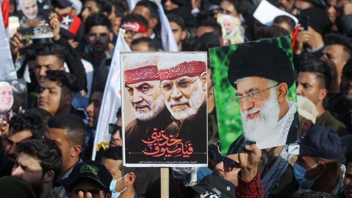 Iraqi demonstrators lift a placards depicting Iraqi commander Abu Mahdi al-Muhandis (C) and Iranian Revolutionary Guards commander Qasem Soleimani (L) and Iran's Supreme Leader Ayatollah Ali Khamenei (R), in Tahrir square in the capital Baghdad on January 3, 2021. (AFP)