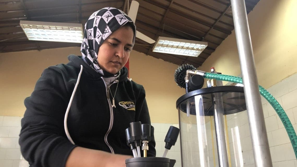 Lekaa El Kholy, Egypt's first female mechanic, checks auto engine oil changer at her new maintenance center in Luxor city on January 2, 2020. (Reuters)